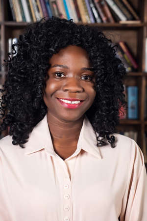Portrait of an african american woman in a blouse on the background of shelves with books.