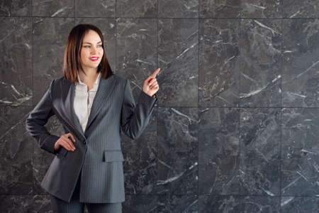 Young brunette in business gray suit, points to copy space.
