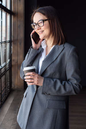 Business woman with coffee stands by the window and speaks on the phone. Foto de archivo