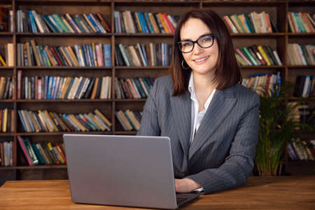 Beautiful woman in formal suit sits at a table with a laptop, copy space. Standard-Bild