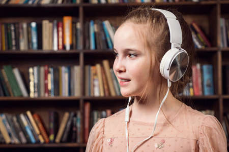 Teenage girl in white headphones smiling looks to the side.
