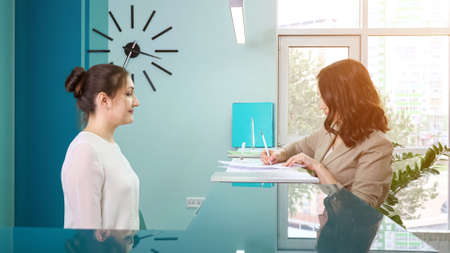 Lady office manager in white blouse shows registration book to woman client standing at reception in contemporary hospital close side view