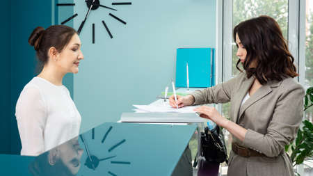 Lady office manager in white blouse shows registration book to woman client standing at reception in contemporary hospital side view