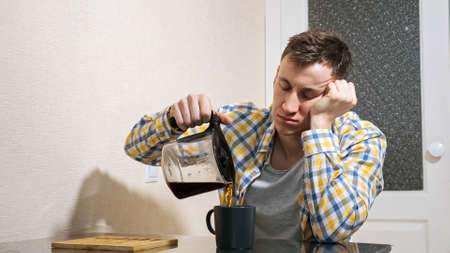 Sleepy man pours coffee while sitting at the table in the kitchen. Stock fotó