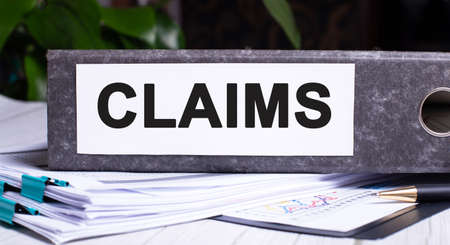 CLAIMS is written on a gray file folder next to documents. Business concept Banque d'images