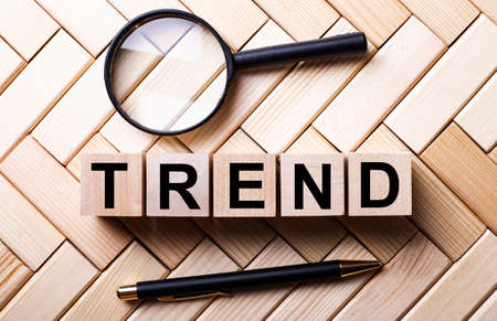 TREND word is made up of wooden cubes near a magnifying glass and a fountain pen on a wooden background. Marketing concept