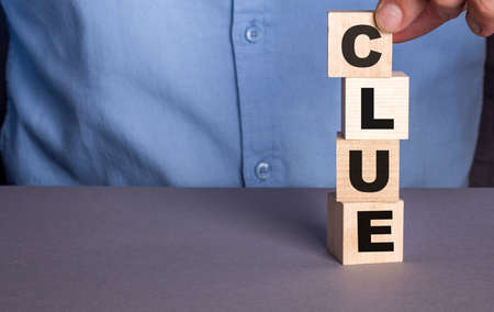 The word CLUE the man composes from wooden cubes vertically.
