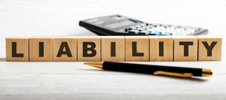 The word LIABILITY is written on the wooden cutouts between the calculator and the pen on a light background.