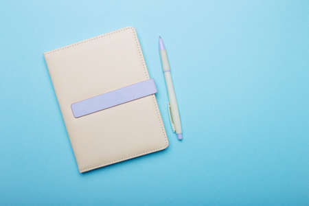 Beige notepad with a pen lie on a light blue background. Copy space 版權商用圖片