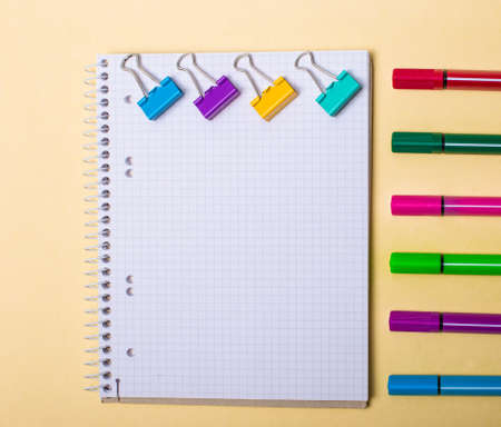 A blank notepad, multi-colored paper clips and markers lie on a beige background. Copy space 版權商用圖片