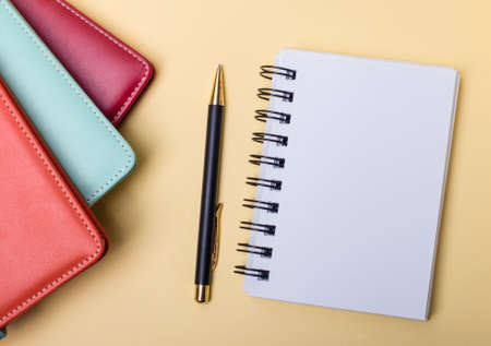 Multi-colored diaries lie on a beige background near a blank notebook and a pen. Flat lay. Copy space 版權商用圖片