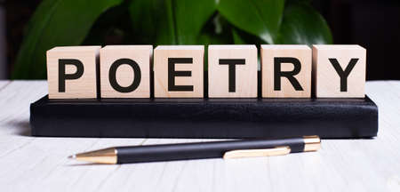 The word POETRY on wooden cubes on a diary near the pen on a green background.