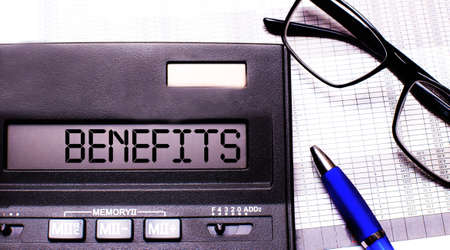 The word BENEFITS is written in the calculator near black-framed glasses and a blue pen. Archivio Fotografico
