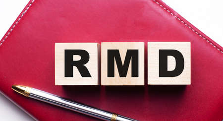 RMD is made up of wooden cubes that stand on a burgundy notebook near the pen. Business concept