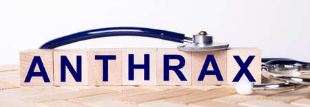 The word ANTHRAX is written on wooden cubes near a stethoscope on a wooden background. Medical concept