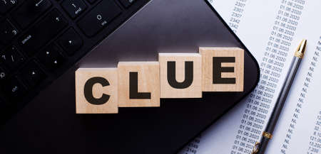 The word CLUE is written on wooden cubes on the keyboard next to the pen.