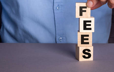 A man in a blue shirt composes the word FEES from wooden cubes vertically