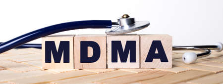 Wooden cubes with the word MDMA on a wooden background and a stethoscope on them. Medical concept Stok Fotoğraf
