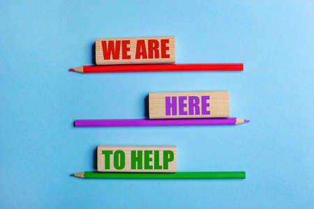 On a blue background, three colored pencils, three wooden blocks with text WE ARE HERE TO HELP Banco de Imagens