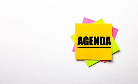 On a light background - bright multicolored stickers with the text AGENDA. Copy space