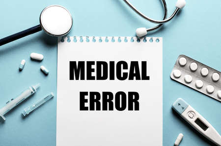 MEDICAL ERROR written on a white notepad on a blue background near a stethoscope, syringe, electronic thermometer and pills. Medical concept