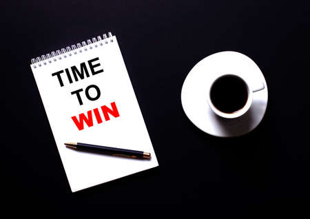 TIME TO WIN is written in a white notebook in red type near a white cup of coffee on a black table. Motivational concept