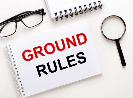 GROUND RULES is written in a white notebook on a light background near the notebook, black-framed glasses and a magnifying glass.