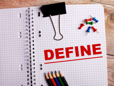 The word DEFINE is written in a notebook near multi-colored pencils and buttons on a wooden background.