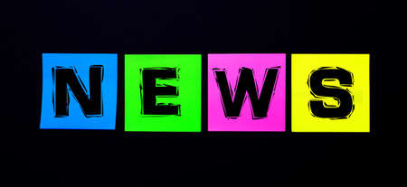 On a black background, bright multicolored stickers with the word NEWS Banque d'images
