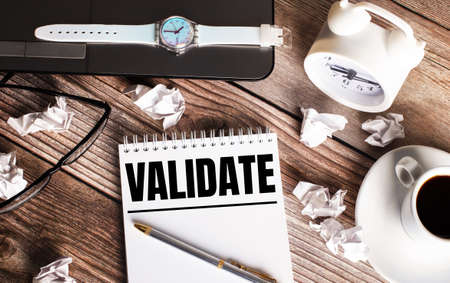 There is a cup of coffee on a wooden table, a clock, glasses and a notebook with the word VALIDATE. Business concept