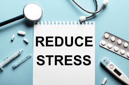 The word REDUCE STRESS written on a white notepad on a blue background near a stethoscope, syringe, electronic thermometer and pills. Medical concept