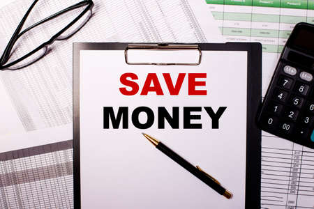 SAVE MONEY is written on a white sheet of paper, near the glasses and the calculator.
