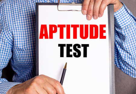 The man points with a pen to the text APTITUDE TEST on a white sheet.