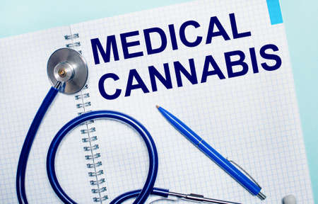 On a light blue background, an open notebook with the words MEDICAL CANNABIS, a blue pen and a stethoscope. View from above.