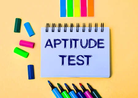 On a beige background, a notebook with the words APTITUDE TEST, bright felt-tip pens and stickers Banque d'images