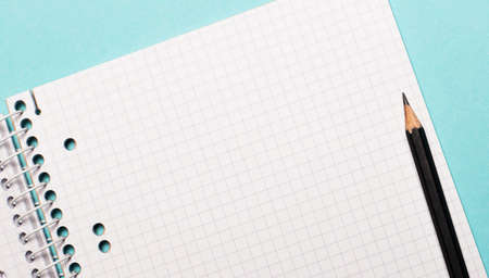On a light blue background, a squared notebook with a place to insert text or illustrations and a black pencil
