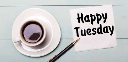 On a light blue wooden tray, there is a white cup of coffee, a handle and a napkin that says HAPPY TUESDAY.