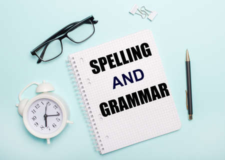 On a light blue background lie black glasses and a pen, a white alarm clock, white paper clips and a notebook with the words SPELLING AND GRAMMAR. Business concept