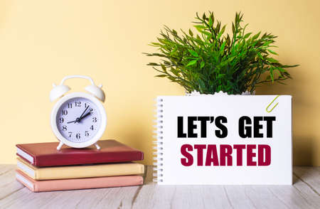 LET'S GET STARTED is written in a notebook next to a green plant and a white alarm clock, which stands on colorful diaries.