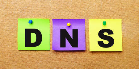 On a beige background, multi-colored stickers for notes with the word DNS Domain Name System