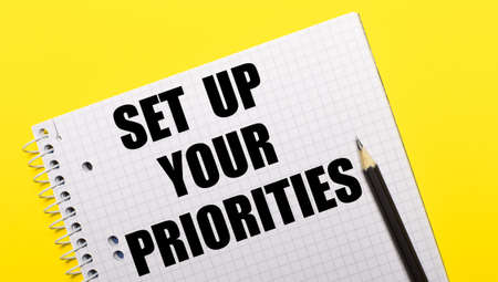 White notebook with SET UP YOUR PRIORITIES written in black pencil on a bright yellow background.