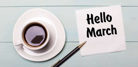 On a light blue wooden tray, there is a white cup of coffee, a handle and a napkin that says HELLO MARCH.