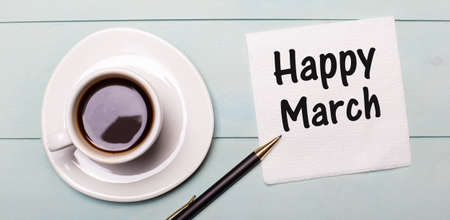 On a light blue wooden tray, there is a white cup of coffee, a handle and a napkin that says HAPPY MARCH