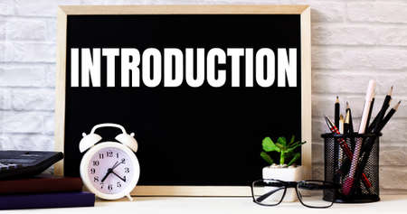 The word INTRODUCTION is written on the chalkboard next to the white alarm clock, glasses, potted plant, and pencils in a stand.