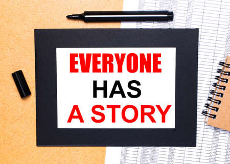 On a wooden table, there is a black open marker, a brown notepad and a sheet of paper in a black frame with the text EVERYONE HAS A STORY. View from above.
