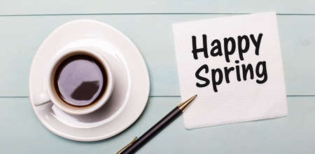 On a light blue wooden tray, there is a white cup of coffee, a handle and a napkin that says HAPPY SPRING