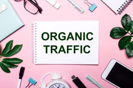 ORGANIC TRAFFIC is written in a white notebook on a pink background surrounded by business accessories and green leaves.