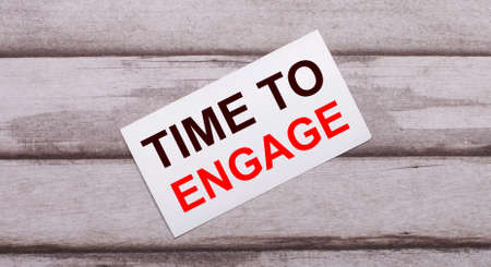 On a wooden background, there is a white card with red text TIME TO ENGAGE
