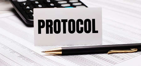 On the table there are reports, a pen, a calculator and a white card with the text PROTOCOL. Defocus Archivio Fotografico