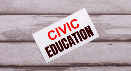 On a wooden background, there is a white card with red text CIVIC EDUCATION